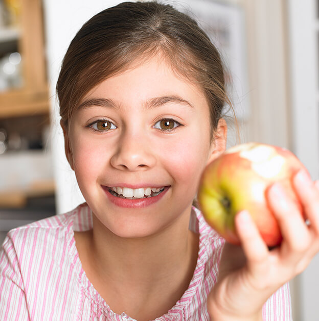 smiling young girl holding an apple
